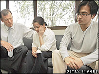 Australia's Victoria state Attorney-General Rob Hulls (L) comforts a weeping Kim Nguyen (C) while her son Khoa Nguyen looks on at the Australian High Commission on November 24, 2005
