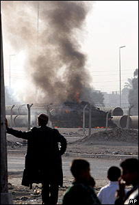 A US armoured vehicle burns in Baghdad after a bomb attack on 28 November