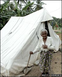 Sri Lankan tsunami survivor and seashore resident Jasiling, 89, emerges from her temporary shelter tent in a camp in Telewatta