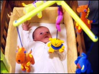 Baby playing with colourful mobile
