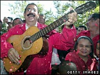 Surrounded by supporters, opposition candidate Manuel Zelaya plays the guitar after casting his vote