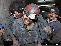 A trapped miner of Dongfeng Coal Mine is carried out by his fellow workers