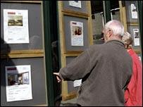 People looking in an estate agents window