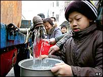 A young boy fills a water container from a tanker truck in a street in Harbin a day before the mains supply was officially declared safe