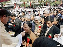 Cardinal Crescenzio Sepe  distributes holy communion to the faithful at the end of an ordination ceremony outside Hanoi's cathedral, 29 November 2005.