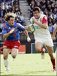 Biarritz's Damien Traille races clear of Stade Francais' Mauro Bergamasco to score