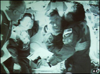 Italian astronaut Roberto Vittori (centre) and Russian cosmonaut Salizhan Sharipov (right) embrace each other on board the international space station