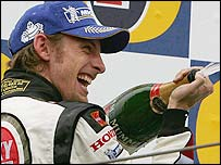 Jenson Button celebrates his third place on the podium at Imola