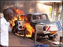 Man looks at burning car in Kampala