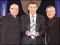 Tony Mowbray receives his award from Stuart Cosgrove & Tam Cowan