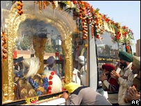 Sikhs offer prayers outside a gold-plated wooden palanquin carrying the Guru Granth Sahib as it crosses the India-Pakistan joint check post at Wagah