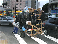 "A ""catador de lixo"" (rubbish scavenger) pulls his cart through Sao Paulo city centre"