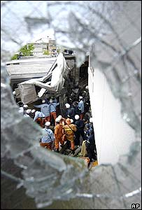 Rescuers conduct a rescue operation seen through a glass which was broken after a commuter train hurtled into an apartment complex in Amagasaki, western Japan, Monday, April 25, 2005