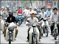 Motorcyclists ride past national and communist flags on a street in Ho Chi Minh city, 24 April 2005.