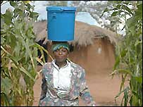 Woman carries a bucket of water on her head
