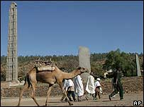 Camels walk past Axum obelisk