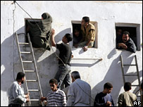 Egyptian voters use ladders to get into a polling station in Bosat