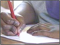 Child's hand writing on a desk