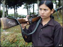 A Nepalese Maoist guerrilla woman holds a rifle while watching an armed exercise in Bhojpur, eastern Nepal