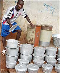Muhammed Saidy with a display of saucepans made from recycled metal