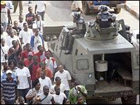 Demonstrators march past police in Libreville, 1 December 2005