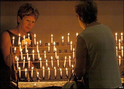 Women light prayer candles during a vigil in Melbourne