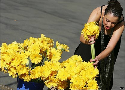 Woman arranges yellow flowers at a vigil in Sydney