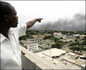 Man points towards smoke billowing from various parts of Lome following clashes