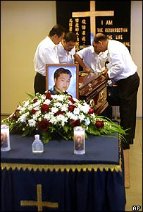 Undertakers adjust the coffin of Nguyen Tuong Van after his execution