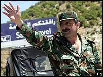 Syria soldier waves before crossing Syria-Lebanese border