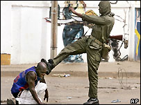 Soldier kicking a protester on the streets of the Togolese capital,  Lome