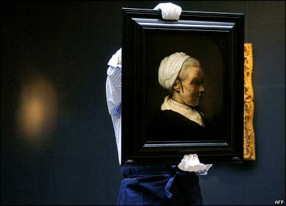 A Sotheby's employee carries 'Elderly Woman in a White Bonnet' by Rembrandt.