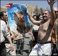 A Lebanese man waves a poster of slain premier Rafik Hariri during celebrations at the Lebanese-Syrian border crossing point of Masnaa