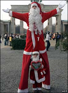 The world's tallest and shortest working Santa Clauses pose in front of the Brandenburg Gate in Berlin, Germany