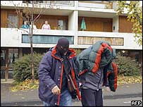 French policeman escorts a suspected Islamic radical in November 2005 in Bourges