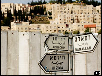 A Jewish settlement is seen on the hill behind Israel's barrier as road signs for the Palestinian towns of Jericho, Ramallah, and Hizma are seen in front