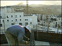 A worker builds part of a construction site in the West Bank settlement of Maale Adumin