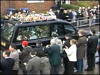 People applaud as the coffin passes by