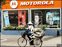 A woman rides past a Motorola mobile phone shop in downtown Ho Chi Minh City
