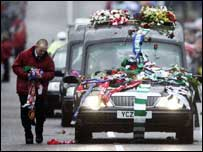 The crowd threw flowers and scarves onto the hearse