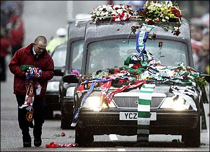 Scarves and flowers mount up on the bonnet of the hearse