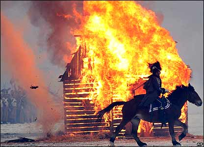 A rider goes by a burning house