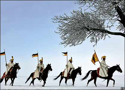 Cavalrymen gallop through the snow as several thousand military history enthusiasts from 23 countries are gathering at the Slavkovo