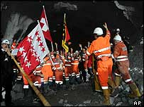 Engineers and workers cheer after tunnel breakthrough
