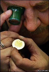 Worker examines a euro coin