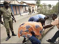 Residents of the Togolese capital Lome clean up the streets under the supervision of a soldier