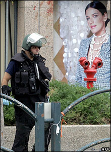 A policeman by a blood-splattered hoarding at the scene of the bombing