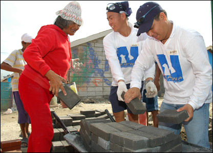 Nestle employees and slum residents help build accommodation with sponsorship money and time from company employees.