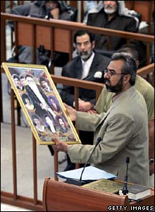 Ahmed Hassan Mohammed holds pictures of deceased relatives, during the trial of Saddam Hussein