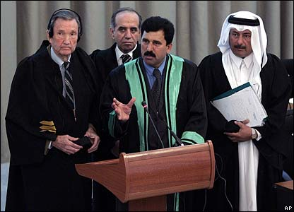 Head lawyer Khalil Dulaimi, surrounded by advisers, addresses the court during the trial of Saddam Hussein